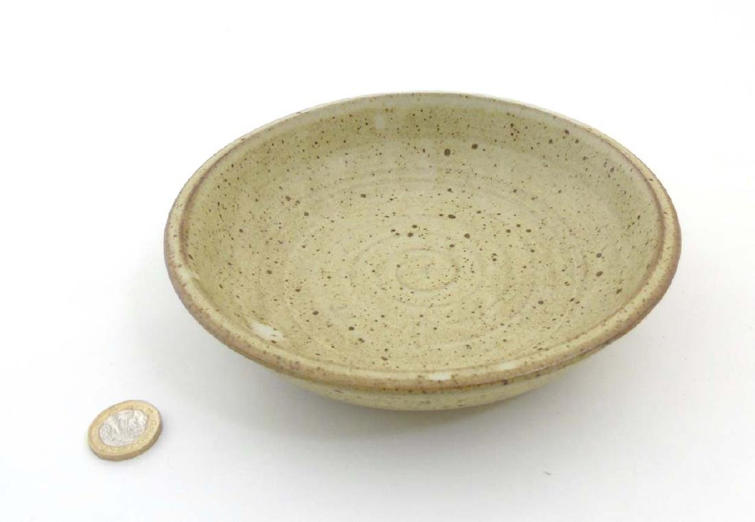 A studio pottery bowl of beige tones decorated with