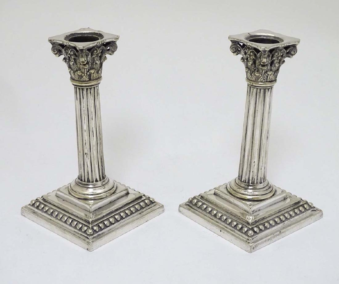 A pair of silver plate candlesticks of Corinthian
