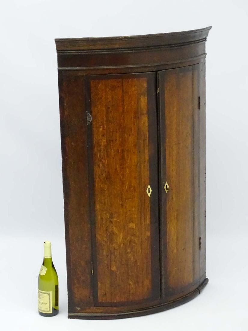 A late 18thC oak bow fronted corner cupboard with