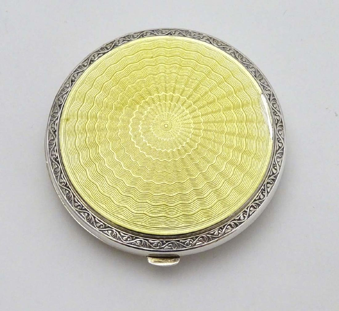 A silver powder compact with yellow guilloche enamel