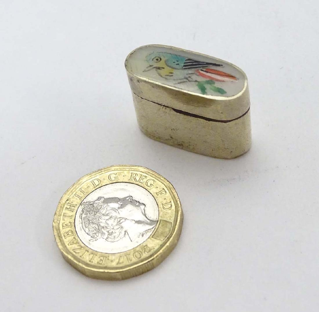 A silver plate small pill box of ovoid form with image