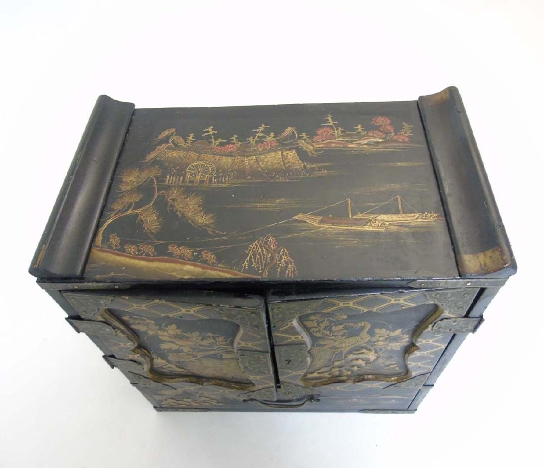 An Ornate Japanese table cabinet opening to reveal - 2