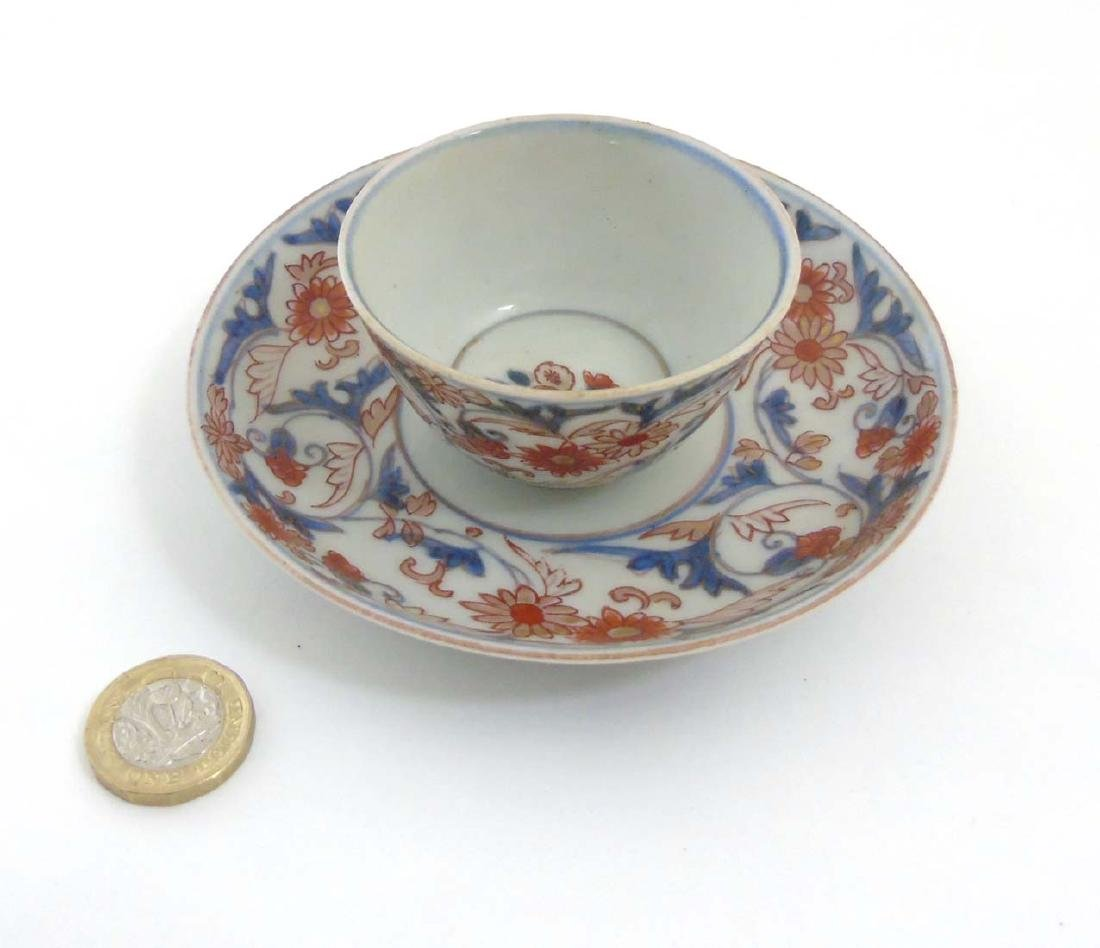A Japanese Imari cup and saucer, decorated in blue