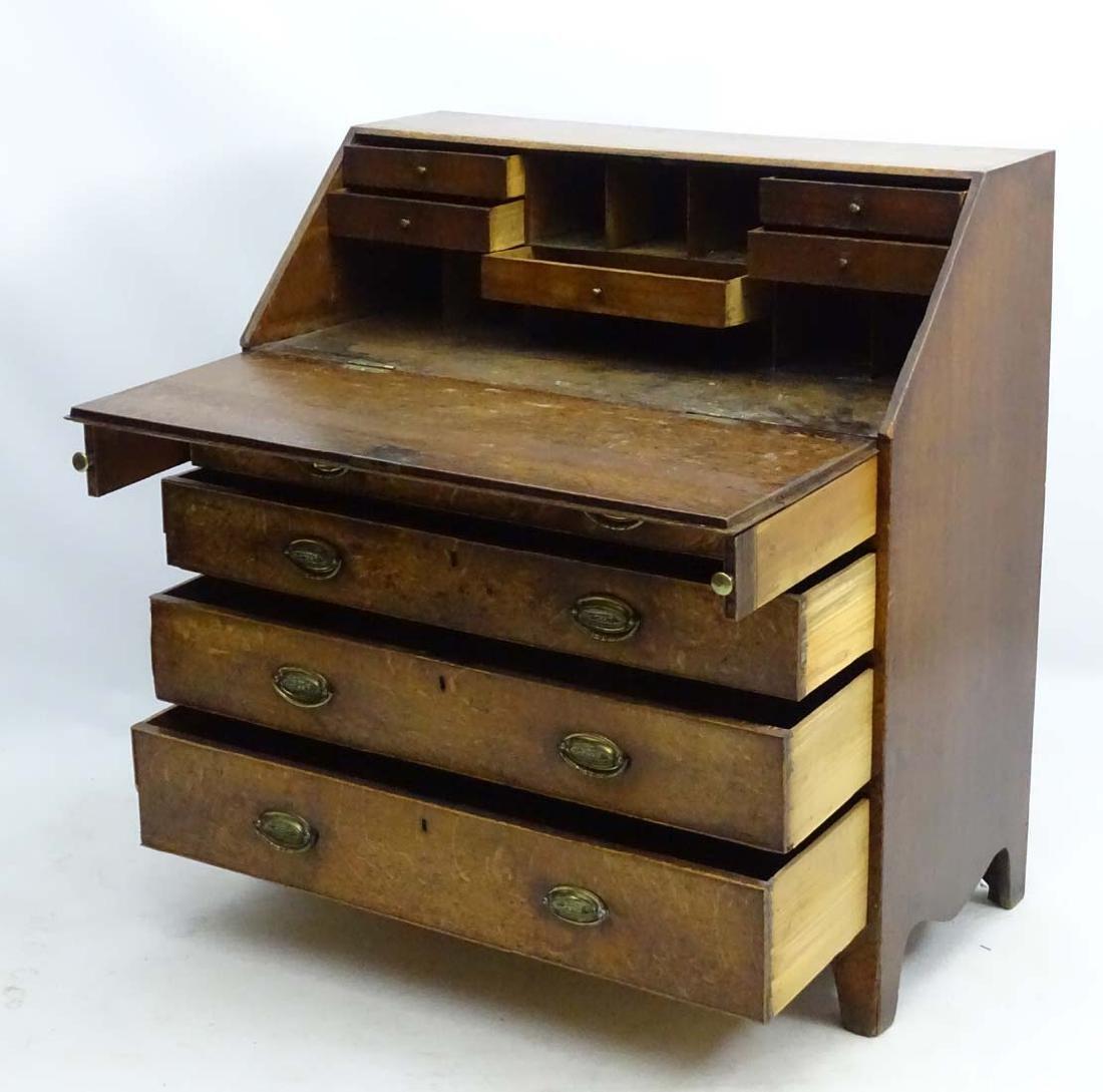 A Georgian oak bureau with four long drawers and a - 8