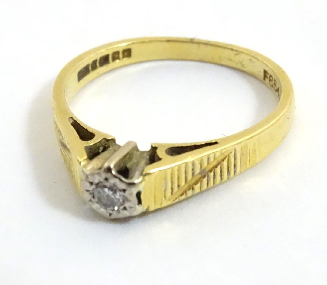 An 18ct gold ring set with central diamond