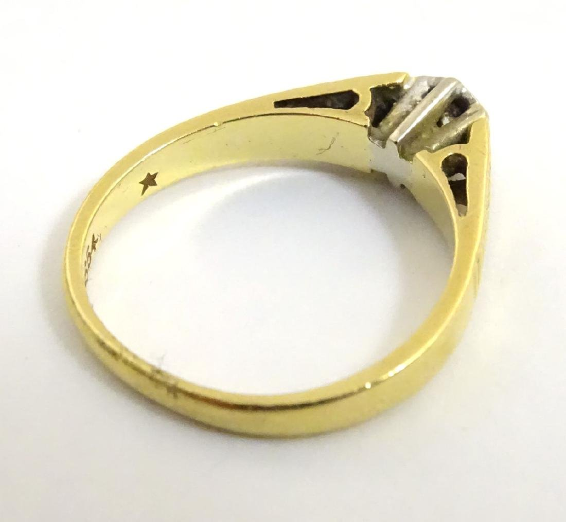 An 18ct gold ring set with central diamond - 2