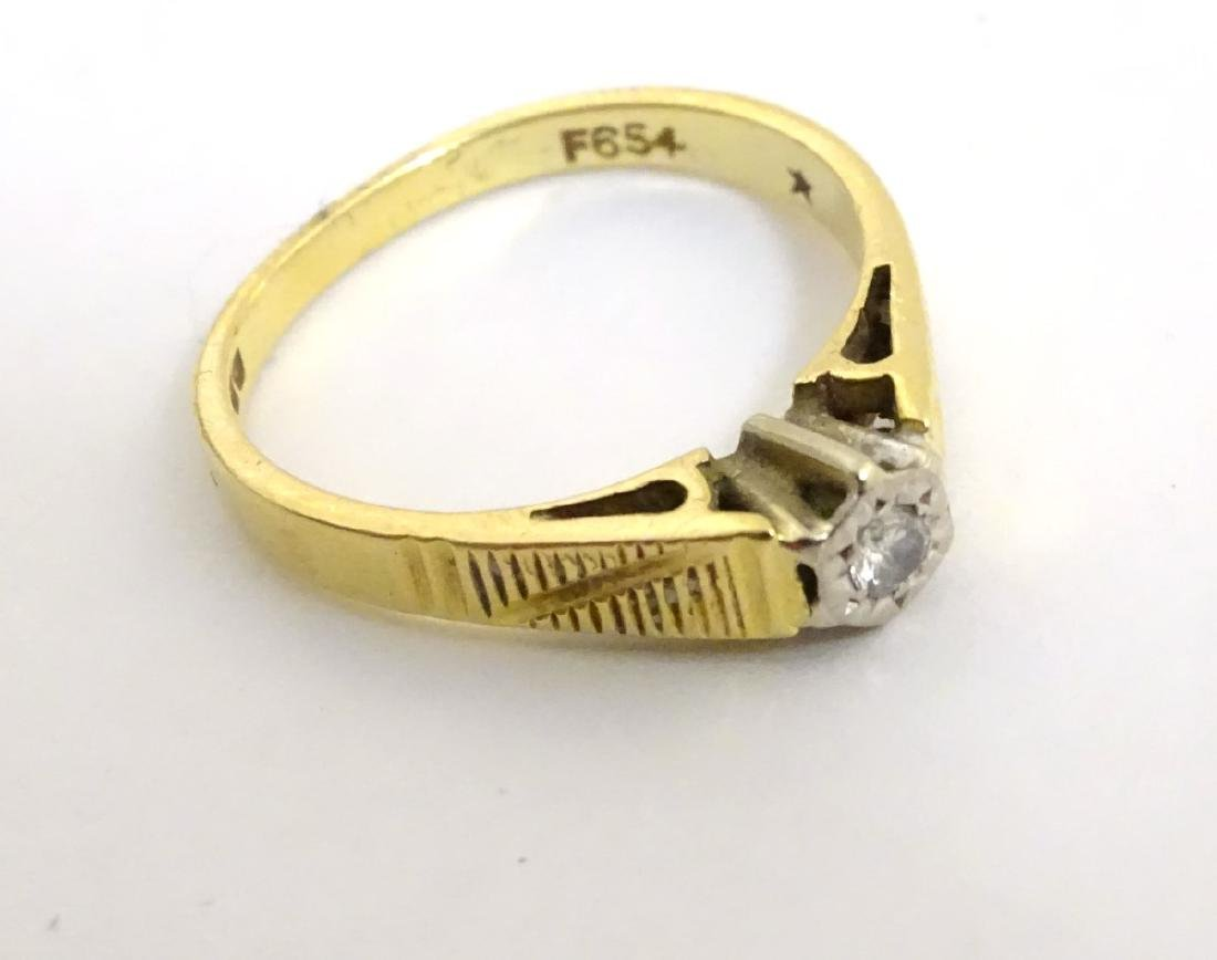 An 18ct gold ring set with central diamond - 3