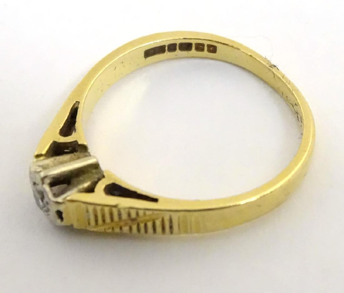 An 18ct gold ring set with central diamond - 4