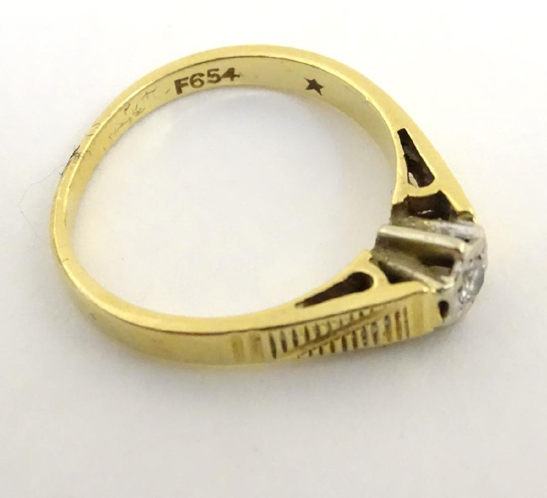 An 18ct gold ring set with central diamond - 5
