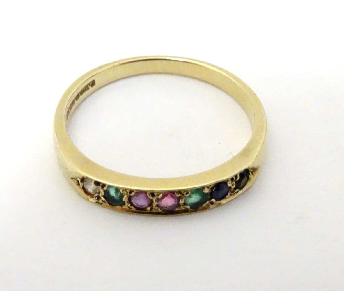 A 9ct gold ring set with band of coloured stones