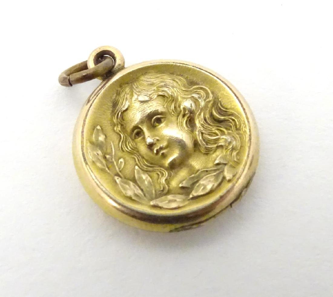 A gilt metal pendant locket with decoration to one side