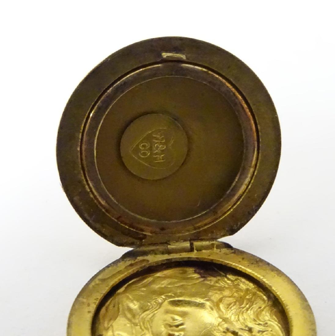 A gilt metal pendant locket with decoration to one side - 2