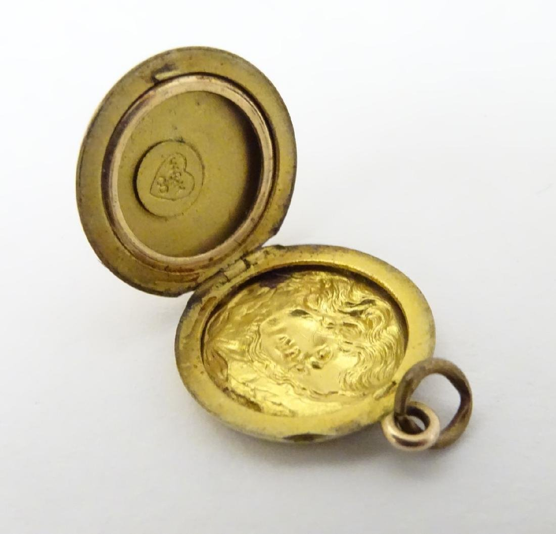 A gilt metal pendant locket with decoration to one side - 5