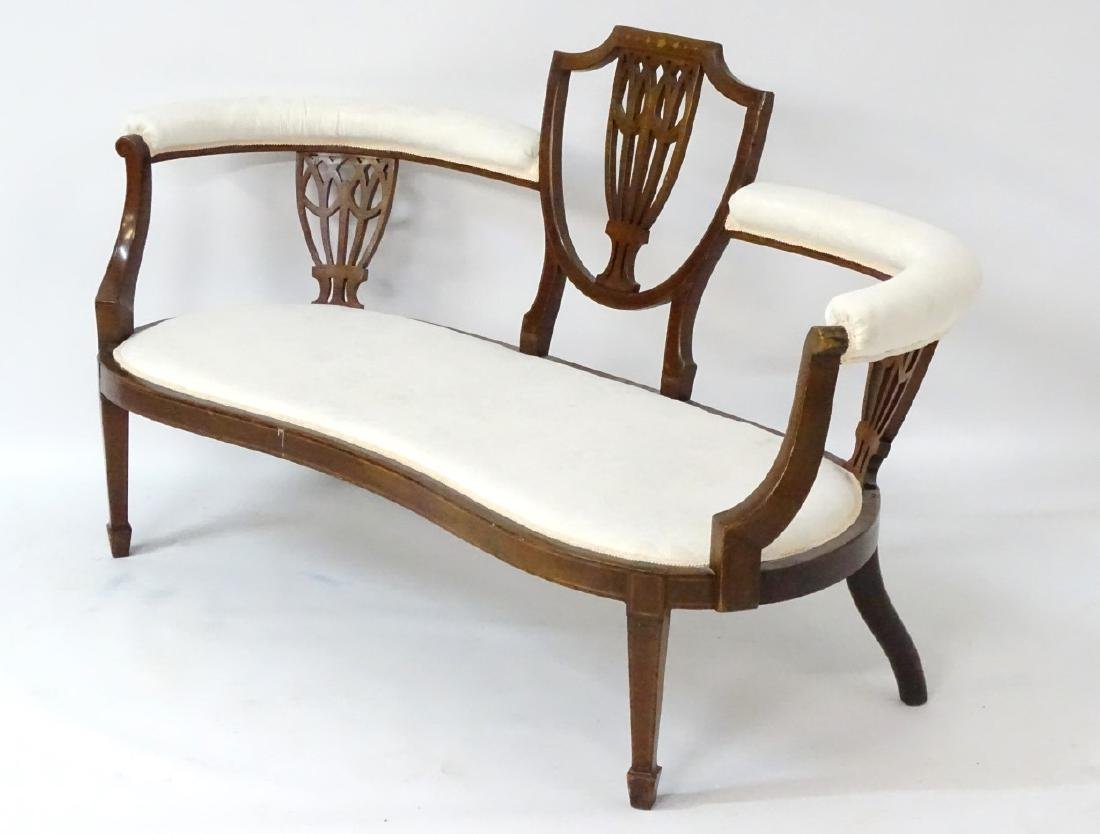 An early 20thC conversational sofa with curved