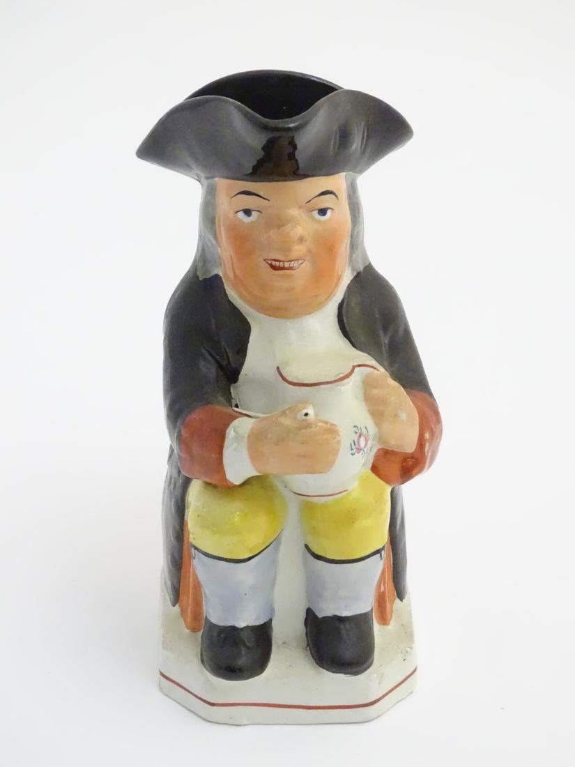 A 19thC Staffordshire Toby jug formed as a man seated