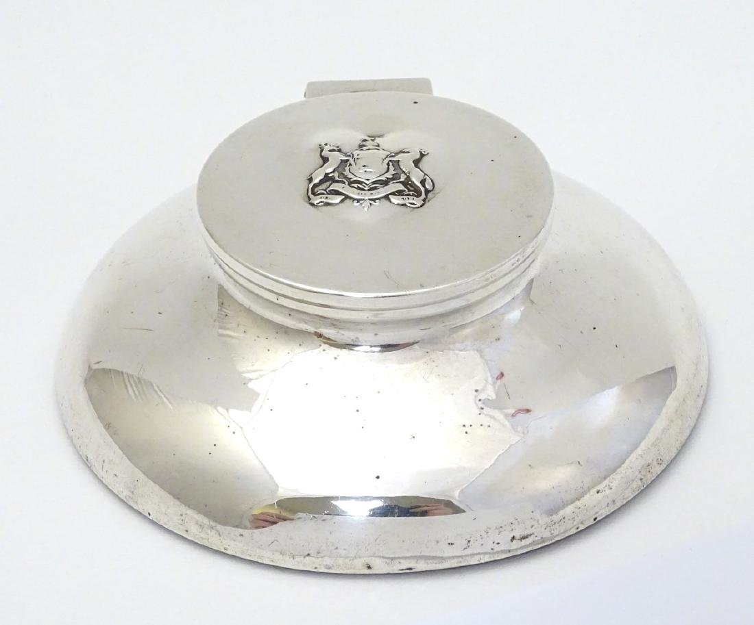 A silver inkwell of capstan form with coat of arms to