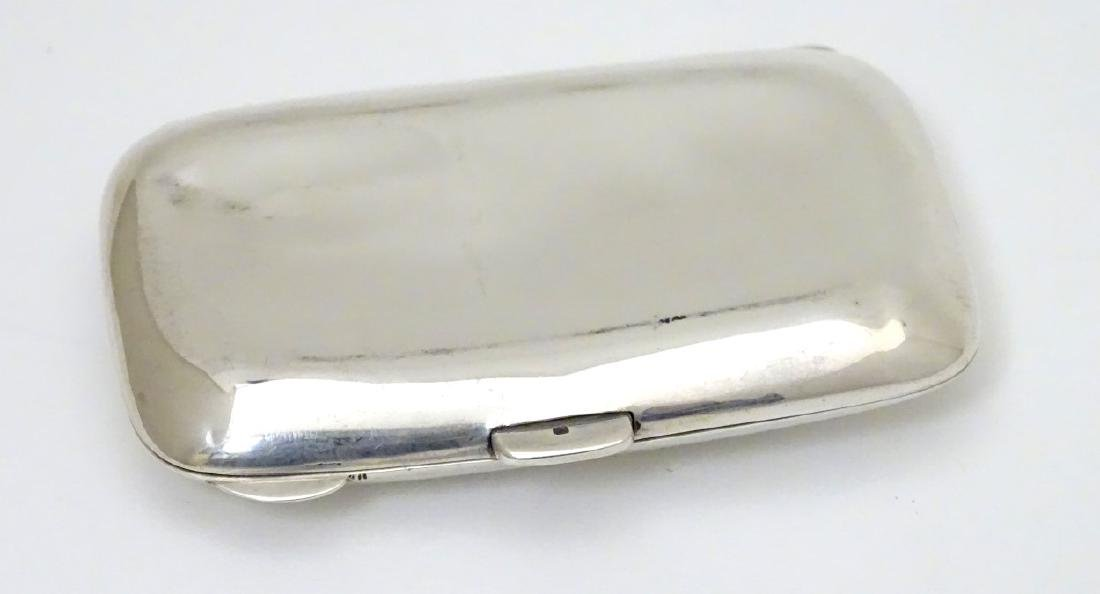 A silver cigarette case hallmarked Birmingham 1924 - 3