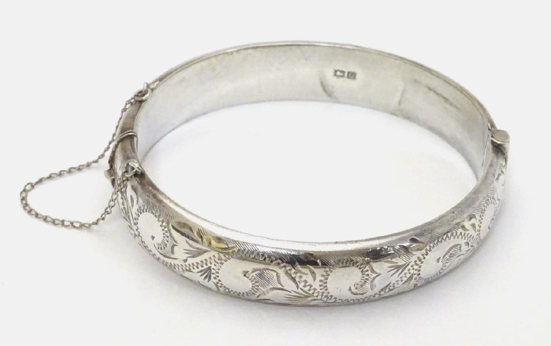 A silver bangle bracelet with engraved decoration.