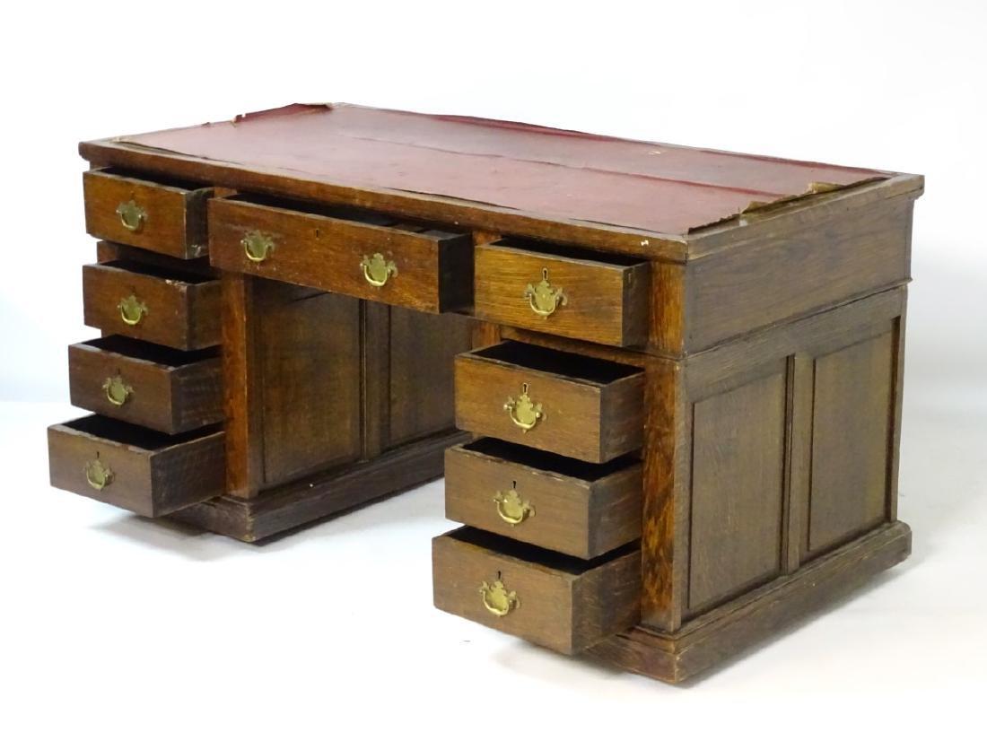 An early 20thC oak pedestal desk comprising a single - 6