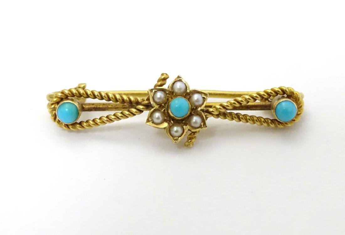 A c.1900 gold and gilt metal brooch set with turquoise