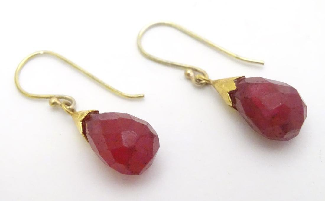 A pair of gilt metal drop earrings set with facet cut