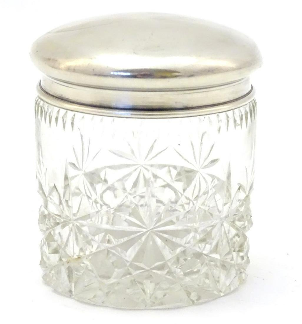 A cut glass dressing table jar with silver top