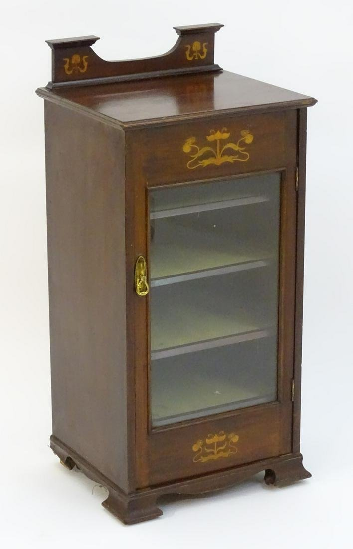 An early 20thC mahogany music cabinet with a shaped up