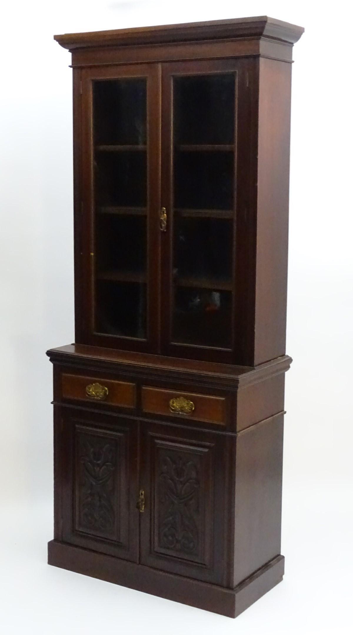 An Edwardian mahogany glazed bookcase, having a moulded