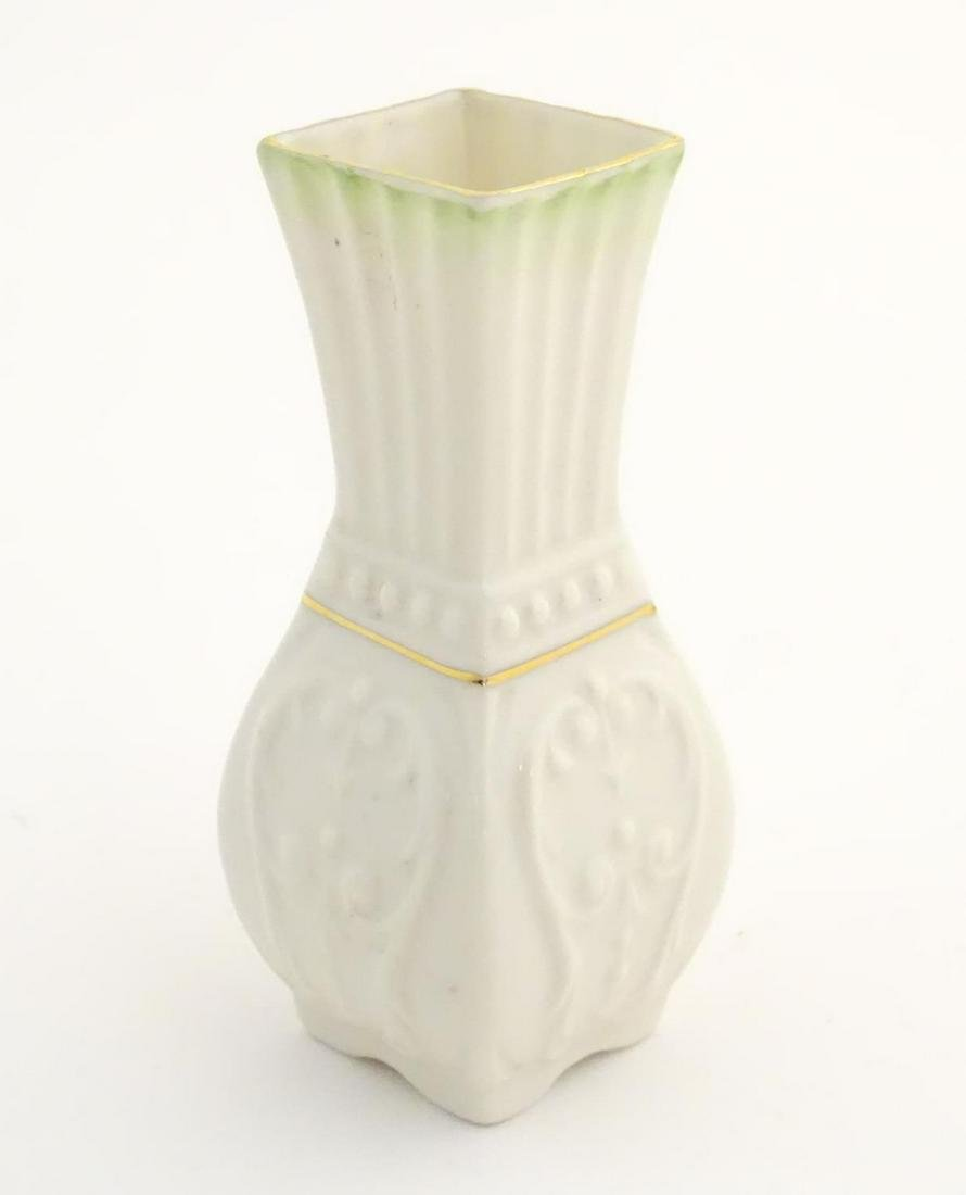 A small Belleek bud vase of squared form with fluted