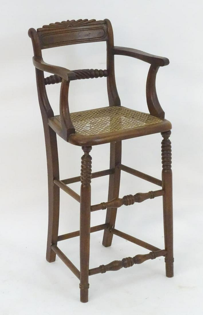 A 19thC walnut child's chair with a carved cresting