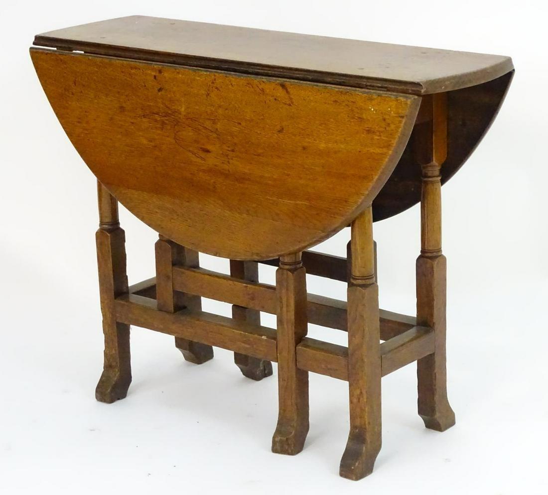 A late 19thC oak gateleg table, having drop flaps