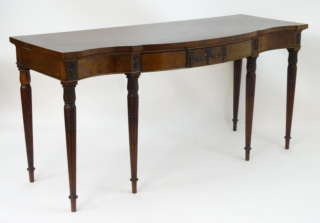 An early 20thC mahogany sideboard with a shaped top, a