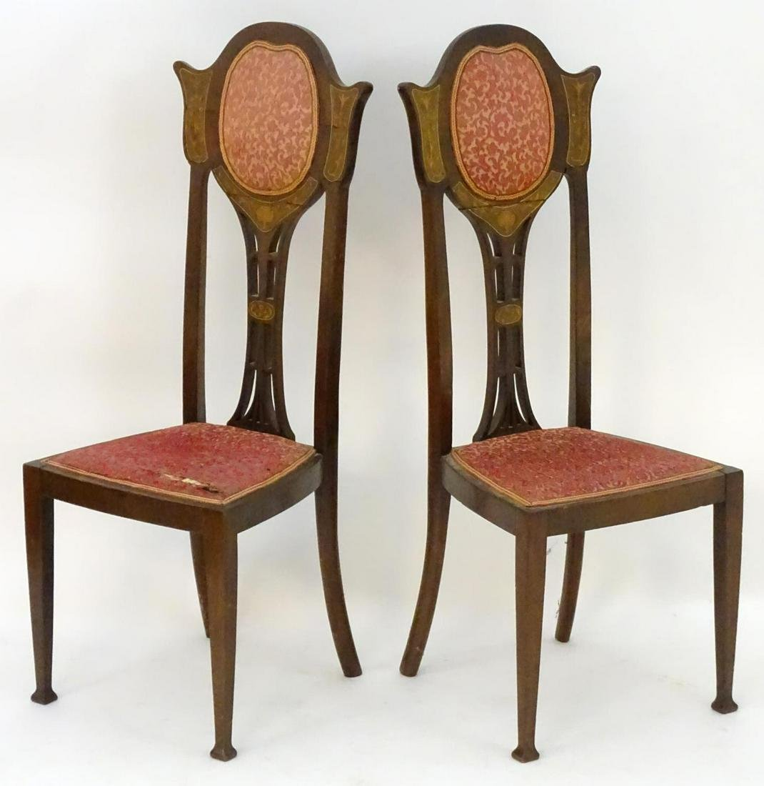 A pair of early 20thC Art Nouveau chairs with shaped