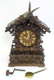 A 19thC Black Forest carved wood cuckoo table clock in