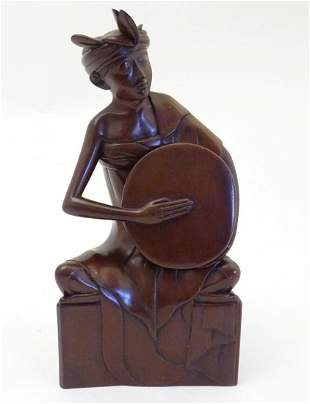 An Indonesian wooden carving modelled as a seated man