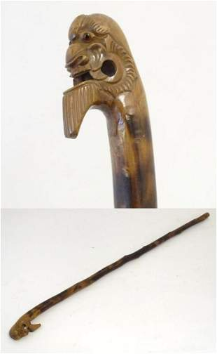 A 20thC Oriental walking cane with a carved head handle
