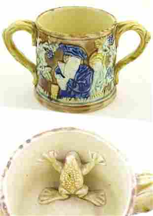 A majolica loving cup / twin handled mug decorated with