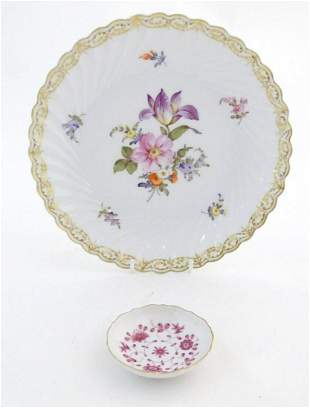 A Nymphenburg plate with a scallop edge and flower