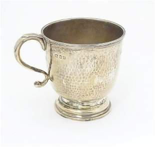 A silver christening mug with hammered decoration.