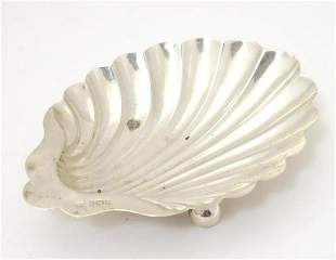 A silver butter dish of scallop shell form. Hallmarked