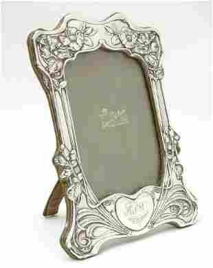 An Art Nouveau silver photograph frame with floral