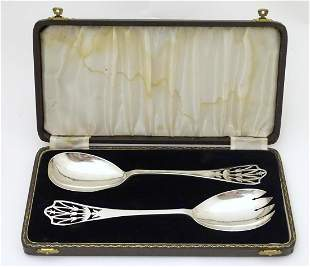 A cased pair of silver servers with fretwork detail to