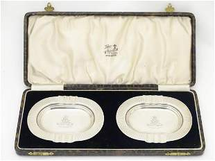 Military Interest : A cased pair of silver ashtrays