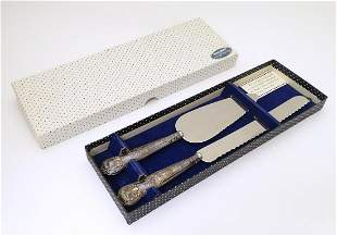 A silver handled pie server together with a silver