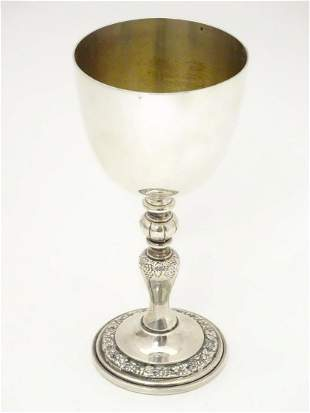 A silver goblet with fruiting vine decoration,