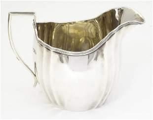 A silver cream jug, hallmarked London 1908, maker C S