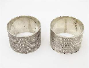 A pair of Art Deco silver napkin rings with engine