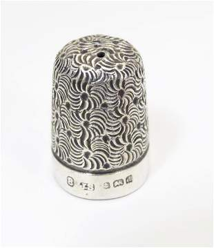 A silver thimble with engraved decoration hallmarked
