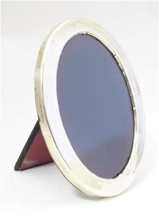 A photograph frame of oval form with silver surround