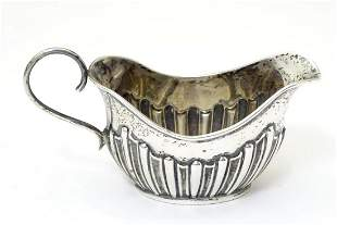 A Victorian silver cream jug with fluted decoration,